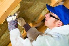 Trabajador que fija el material de aislamiento termal Imagen de archivo