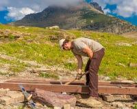 Trabajador que fija el Parque Nacional Glacier del rastro del tablón imagen de archivo libre de regalías