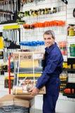 Trabajador que guarda el paquete de la herramienta en la carretilla Imagen de archivo libre de regalías