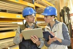 Trabajador que habla con el supervisor en almacén Imagen de archivo libre de regalías