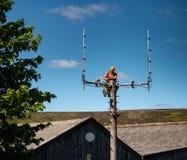 Trabajador que hace alteraciones a un palo de radio de los servicios de emergencia de las ondas imagen de archivo