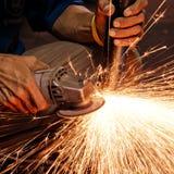Trabajador que hace chispas mientras que suelda con autógena el acero Foto de archivo libre de regalías