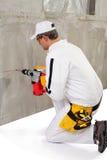 Trabajador que hace un agujero con un perforador Foto de archivo libre de regalías