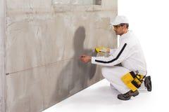 Trabajador que hace una guarnición de la secuencia en la pared del cemento Fotografía de archivo libre de regalías