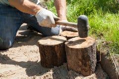 Trabajador que hace una trayectoria del paseo en el jardín adornado con los tocones de madera Imagen de archivo libre de regalías