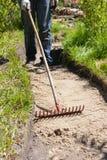 Trabajador que hace una trayectoria del paseo en el jardín adornado con los tocones de madera Foto de archivo libre de regalías