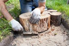 Trabajador que hace una trayectoria del paseo en el jardín adornado con los tocones de madera Imágenes de archivo libres de regalías