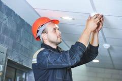 Trabajador que instala el detector de humo en el techo Imagenes de archivo