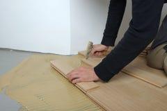 Trabajador que instala el entarimado de madera imagen de archivo