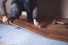 Trabajador que instala el nuevo piso de madera laminado imágenes de archivo libres de regalías