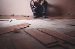 Trabajador que instala el nuevo piso de madera laminado fotografía de archivo libre de regalías