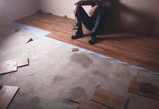Trabajador que instala el nuevo piso de madera laminado imagen de archivo