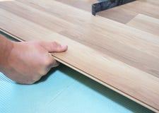 Trabajador que instala el suelo laminado de madera fotos de archivo