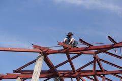 Trabajador que instala la estructura del acero del tejado para la nueva casa en el const Imagenes de archivo