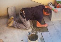 Trabajador que instala las baldosas de cerámica Foto de archivo libre de regalías