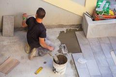 Trabajador que instala las baldosas de cerámica Fotos de archivo