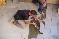 Trabajador que instala las baldosas de cerámica Fotos de archivo libres de regalías