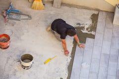 Trabajador que instala las baldosas de cerámica Imagen de archivo libre de regalías