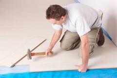 Trabajador que instala un suelo laminado Imágenes de archivo libres de regalías