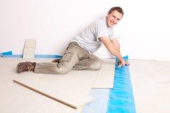 Trabajador que instala un suelo laminado imagen de archivo
