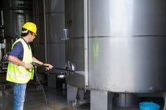 Trabajador que lava el sitio industrial Imagen de archivo