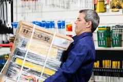 Trabajador que levanta el paquete pesado de la herramienta en tienda del hardware Fotografía de archivo