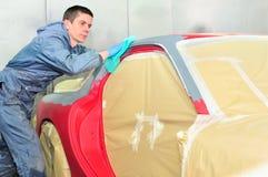 Trabajador que limpia el coche rojo Imagen de archivo libre de regalías