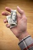 Trabajador que lleva a cabo cientos dólares Imagen de archivo libre de regalías