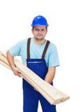 Trabajador que lleva plancks de madera Imagenes de archivo