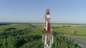 Trabajador que mantiene la antena celular delante de la torre de la telecomunicación