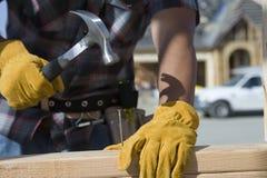 Trabajador que martilla el clavo en el sitio Fotografía de archivo libre de regalías