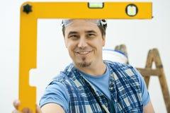 Trabajador que mide con la herramienta llana Imagen de archivo libre de regalías