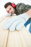 Trabajador que mide el tablón de madera Imagenes de archivo