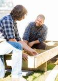 Trabajador que mira la madera de medición del compañero de trabajo el sitio imagen de archivo libre de regalías