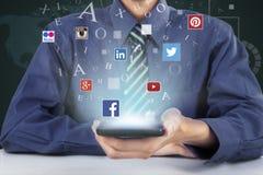 Trabajador que muestra iconos sociales de la red con el teléfono móvil Imagen de archivo libre de regalías