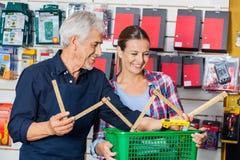 Trabajador que muestra la regla de plegamiento al cliente adentro Imágenes de archivo libres de regalías