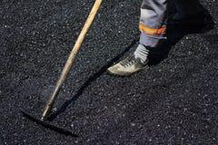Trabajador que nivela el asfalto fresco en un sitio de la construcción de carreteras, indus imágenes de archivo libres de regalías