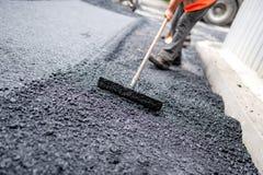 Trabajador que nivela el asfalto fresco en un sitio de la construcción de carreteras Foto de archivo