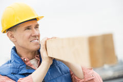 Trabajador que parece ausente mientras que lleva el tablón de madera Imágenes de archivo libres de regalías