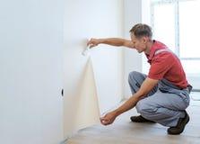Trabajador que pega los papeles pintados Imagen de archivo