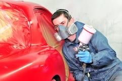 Trabajador que pinta el coche rojo Imagen de archivo libre de regalías