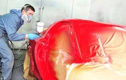 Trabajador que pinta el coche rojo Imágenes de archivo libres de regalías