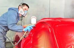 Trabajador que pinta el coche rojo Fotos de archivo libres de regalías