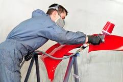Trabajador que pinta el coche rojo de parachoques Foto de archivo libre de regalías