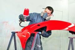 Trabajador que pinta el coche rojo de parachoques Foto de archivo