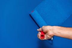 Trabajador que pinta la pared en azul imágenes de archivo libres de regalías