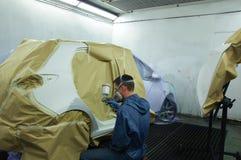 Trabajador que pinta un coche. Fotos de archivo