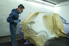 Trabajador que pinta un coche. Imagen de archivo