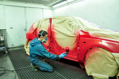 Trabajador que pinta un coche. Fotos de archivo libres de regalías