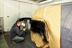 Trabajador que pinta un coche. Fotografía de archivo